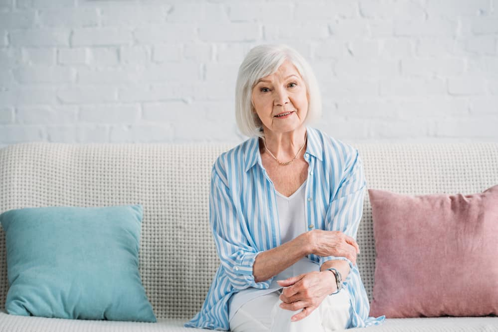 Senior woman sitting on couch at home