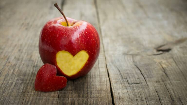 Apple with a heart cut out of it on wood table