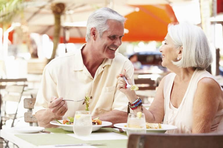 Smiling senior couple eating at outdoor table at restaurant