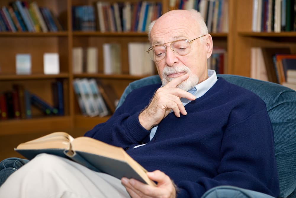 senior man thoughtfully reading book in library